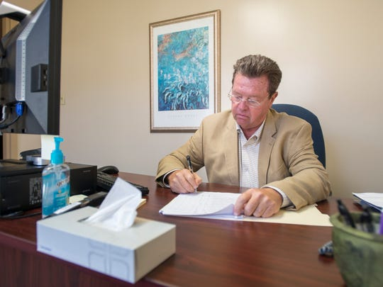Physician Robert Althar goes through a patient's file at the Lakeview Center in Pensacola on Wednesday, July 5, 2017.  Dr. Althar explains that they combine both medication and behavioral therapy when treating clients with opioid addictions.