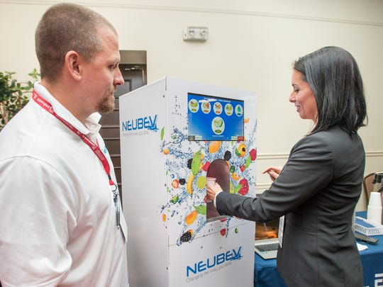 Ross Dahlstrom, of The NeuBev Company, left, looks on as Jacey Cosentino tries a sample of flavored water from a NeuBev dispenser during Entrecon in Pensacola on Tuesday, November 14, 2017.