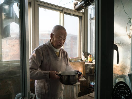 Han holds part of his breakfast, a pot of boiled soy