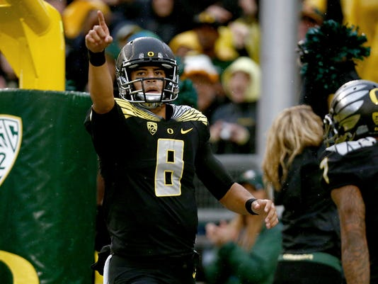 FILE - In this Nov. 1, 2014, file photo, Oregon quarterback Marcus Mariota (8) points to the crowd after scoring a touchdown against Stanford in an NCAA college football game in Eugene, Ore. In his third season leading the Ducks, the 21-year-old from Hawaii has only made headlines for his play. And as good as that has been, he is still a bit of a mystery. (AP Photo/Ryan Kang, File)