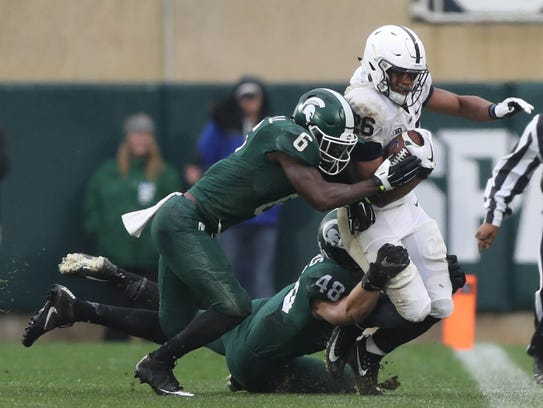 Michigan State's Davis Dowell and Kenny Willekes tackle Penn State's Saquon Barkley during a game on Nov. 4, 2017 at Spartan Stadium in East Lansing.