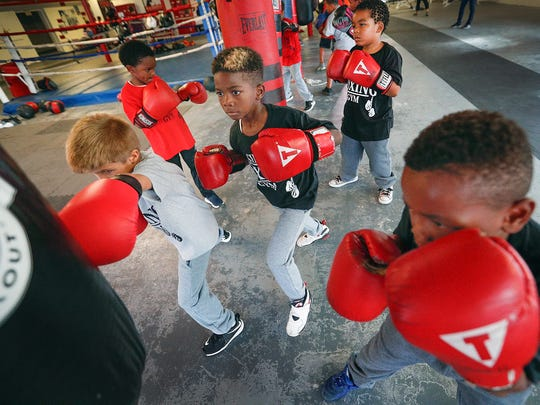 Three young boxing students work the same bag at SIMS Boxing Gym on East 10th Street, Wednesday, Sept. 6, 2017.