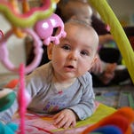Rose Loso, 6 mos., plays with her mobile on the floor at Kelly Martini's in-home child care near Avon. There has been a decline statewide in the number of in-home child care facilities and a shortage, especially in infant care.