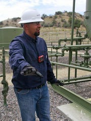 ConocoPhillips optimization technician Juan Cardenas provides a tour of an oil and gas facility in June at a site in Aztec.