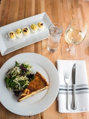 The quiche at Fig in Biltmore Village features caramelized onions, country ham and goat cheese and is served with a green salad.