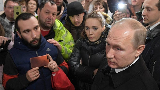 Russian President Vladimir Putin, foreground, listens to locals and relatives of the victims of a fire in a multi-story shopping center in the Siberian city of Kemerovo, about 3,000 kilometers (1,900 miles) east of Moscow, Russia, Tuesday, March 27, 2018.