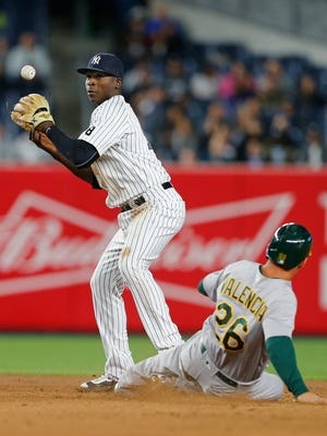 NEW YORK, NY - APRIL 20: Shortstop Didi Gregorius #18 of the New York Yankees loses control of the ball as Danny Valencia #26 of the Oakland Athletics slides in safely on a ball hit by Jed Lowrie #8 during the fourth inning of a game at Yankee Stadium on April 20, 2016  in the Bronx borough of New York City.
