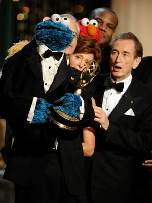 Bob McGrath, right, looks at the Cookie Monster as the accept the Lifetime Achievement Award for 'Sesame Street' at the Daytime Emmy Awards oin 2009.