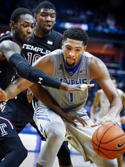 University of Memphis forward Dedric Lawson (left) drives to the basket against Temple University defenders Shizz Alston, Jr. (bottom left) and Mark Williams (top right) during second half action of a 74-62 loss at FedExForum. Lawson grabbed his 17th double-double of this season with a game-high 27 points and 12 rebounds.