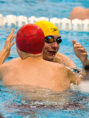 Iowa City West's Will Scott congratulates Iowa City High's Abe Eyman Casey at the end of the 50 yard freestyle race at the IHSAA District Swim Meet at Linn-Mar Acquatic Center in Marion on Saturday, February 7, 2015.
