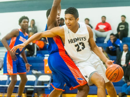 St. Augustine forward Charles Solomon (23) drives to
