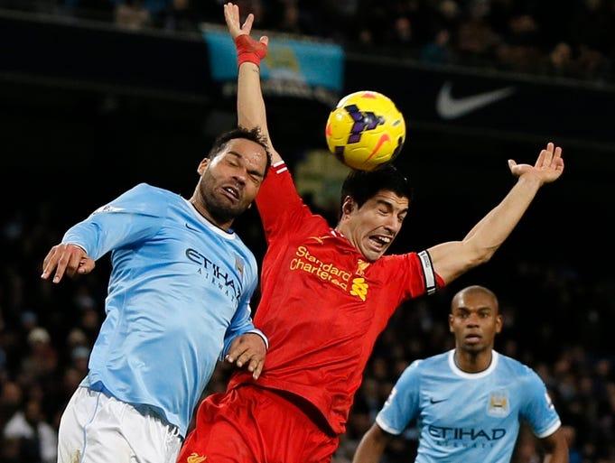 Liverpool striker Luis Suarez is challenged by Manchester City defender Joleon Lescott.