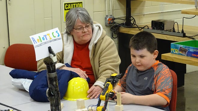 Colton Fleming, 6, of Coshocton, tries to pick up blocks with a robot in an electronics lab at the Coshocton County Career  Center. Colton and his grandmother, Bonnie McVay, of Warsaw, attended an open house at the school Thursday.