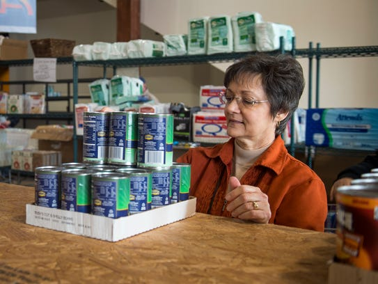 Volunteer Kathleen Klein organizes canned goods at a distribution center in Pigeon Forge on Feb. 13. The distribution center, which provided help to the Sevier County fire victims, closed in February.