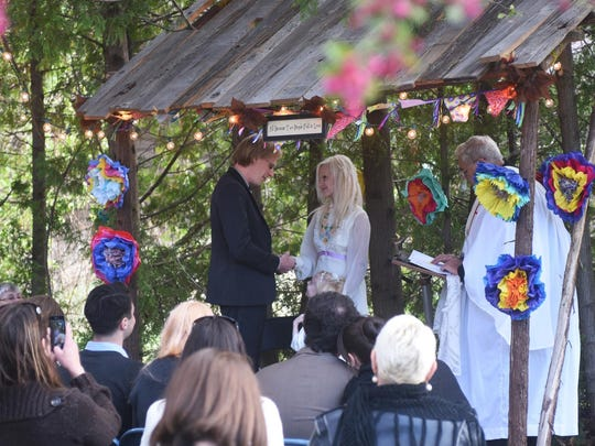 """Steven Link and Katherine Johnson exchange vows May 18 in Sturgeon Bay. The plaque above the couple, which says """"Because two people fell in love,"""" hangs over the kitchen doorway in their house."""