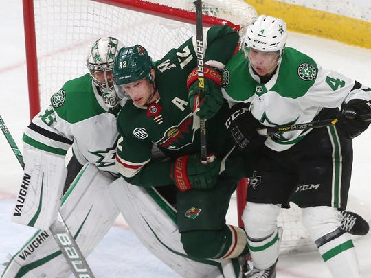 Minnesota Wild's Eric Staal, center, is squeezed between Dallas Stars goalie Anton Khudobin, left, and Miro Heiskanen, of Finland, as he tried to position himself in the second period of an NHL hockey game Thursday, March 14, 2019, in St. Paul, Minn. Khudobin replaced starting goalie Ben Bishop in the second period. (AP Photo/Jim Mone)