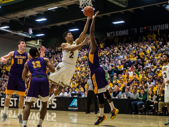 UVM's #2 Trae-Bell Haynes drives the hoop through Albany's