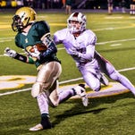 Milford's Brendan Perrett (right) tries to bring down a Howell ball carrier in Friday's 31-14 loss.