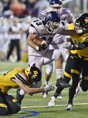 Chambersburg's Clay Myers carries the ball as Red Lion's Zach Crossland, left, dives in to attempt a tackle.