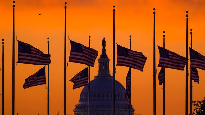 Flags fly at half-staff around the Washington Monument at daybreak in Washington with the US Capitol in the background Monday. President Barack Obama ordered flags lowered to half-staff to honor the victims of the Orlando nightclub shootings.