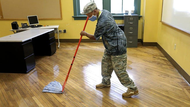 Custodian Mitchell Russell mops a classroom floor in a building at Fort Hayes Arts and Academic High School, 546 Jack Gibbs Blvd., on Thursday, July 9, 2020. Plans for a blended opening this fall of Columbus City Schools buildings for students in grades K-8 may be put on hold amid rising coronavirus cases.