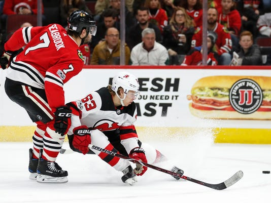 New Jersey Devils left wing Jesper Bratt (63) keeps the puck away from Chicago Blackhawks defenseman Brent Seabrook (7) during the first period of an NHL hockey game Sunday, Nov. 12, 2017, in Chicago. (AP Photo/Kamil Krzaczynski)