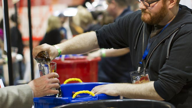 Mark Sarcone pours bottles of beer for New Belgium Brewing during the Hops and Props event in 2013. This year's event is March 10.
