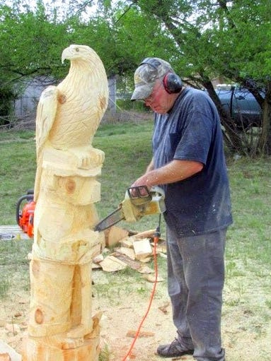 A carver created eagles and others birds as visitors