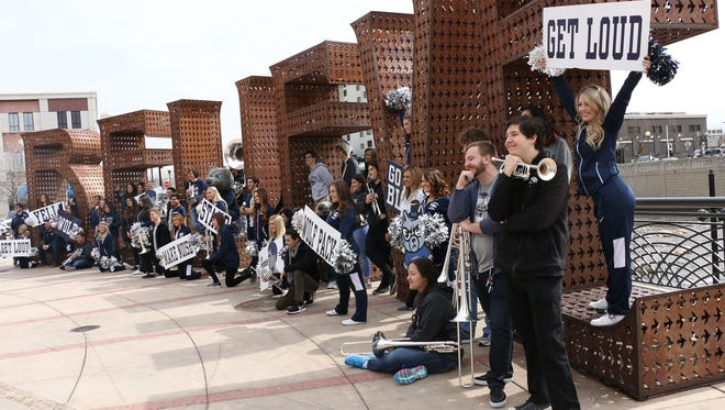 """Members of the Nevada cheer team and band pose for a group shot in front of the """"Believe"""" sign in City Plaza in Reno on March 20, 2018. The group gathered for the photo before heading to join the men's basketball team in Atlanta for the NCAA's Sweet Sixteen."""