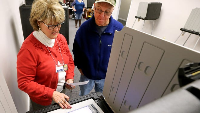 Poll worker Beth Wright shows Alan Leyo how to use the voting machines as Leyo gets ready to vote on the first day of early voting at the Election Commission headquarters on Wednesday, Feb. 10, 2016.