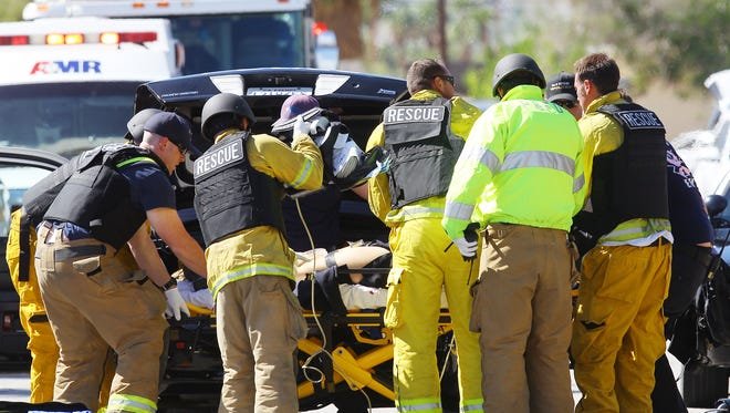 Emergency personnel attend to what appears to be a victim of a gun shot wound on the corner of Cypress Road and Del Lago Road in Palm Springs, California on October 8, 2016.