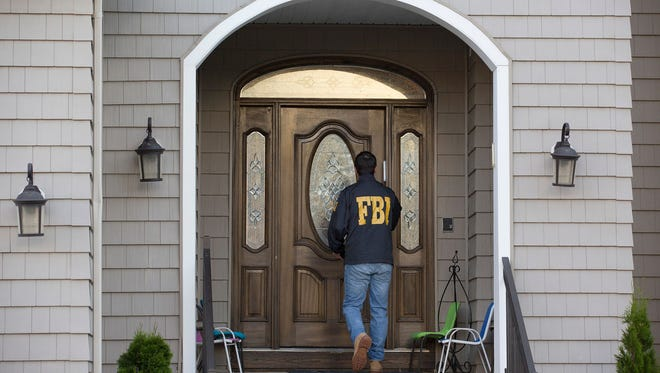 An FBI official tries to make an arrest at the home of Mordechai and Jocheved Breskin in Lakewood Township, N.J., on June 26, 2017. On Thursday, July 6, 2017, the Orange County (N.J.) Prosecutor's Office announced more charges in the ongoing welfare fraud investigation.