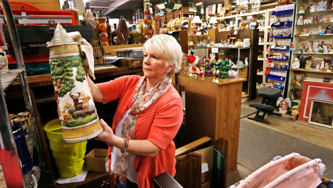 Connie Joy wipes dust off an old beer stein Tuesday, April 3, 2018, at Chestnut Street Mercantile, 231 Chestnut Street in Lafayette. Chestnut Street Mercantile has an eclectic collection of items, from golf clubs, to furniture, to bicycles and more, all for sale. Proceeds benefit the YWCA and it's programs.