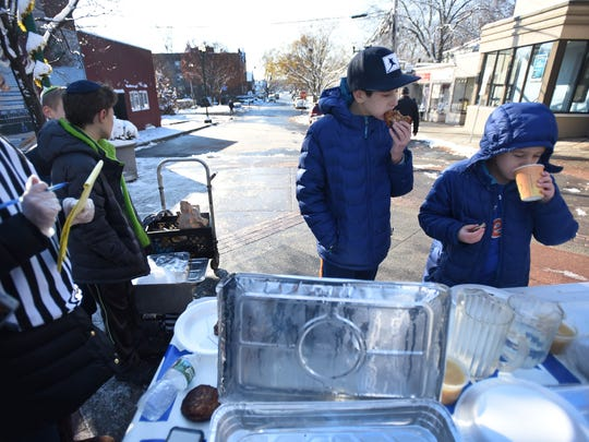 Eitan Danzger, center, 11, of Teaneck and his brother Yehoshua, right, 8, compete with each other during the latke-eating competition in Teaneck on Sunday.