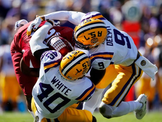 Arkansas running back Devwah Whaley (21) is tackled by LSU linebacker Devin White (40) and safety Grant Delpit (9) in the first half of an NCAA college football game in Baton Rouge, La., Saturday, Nov. 11, 2017. (AP Photo/Gerald Herbert)