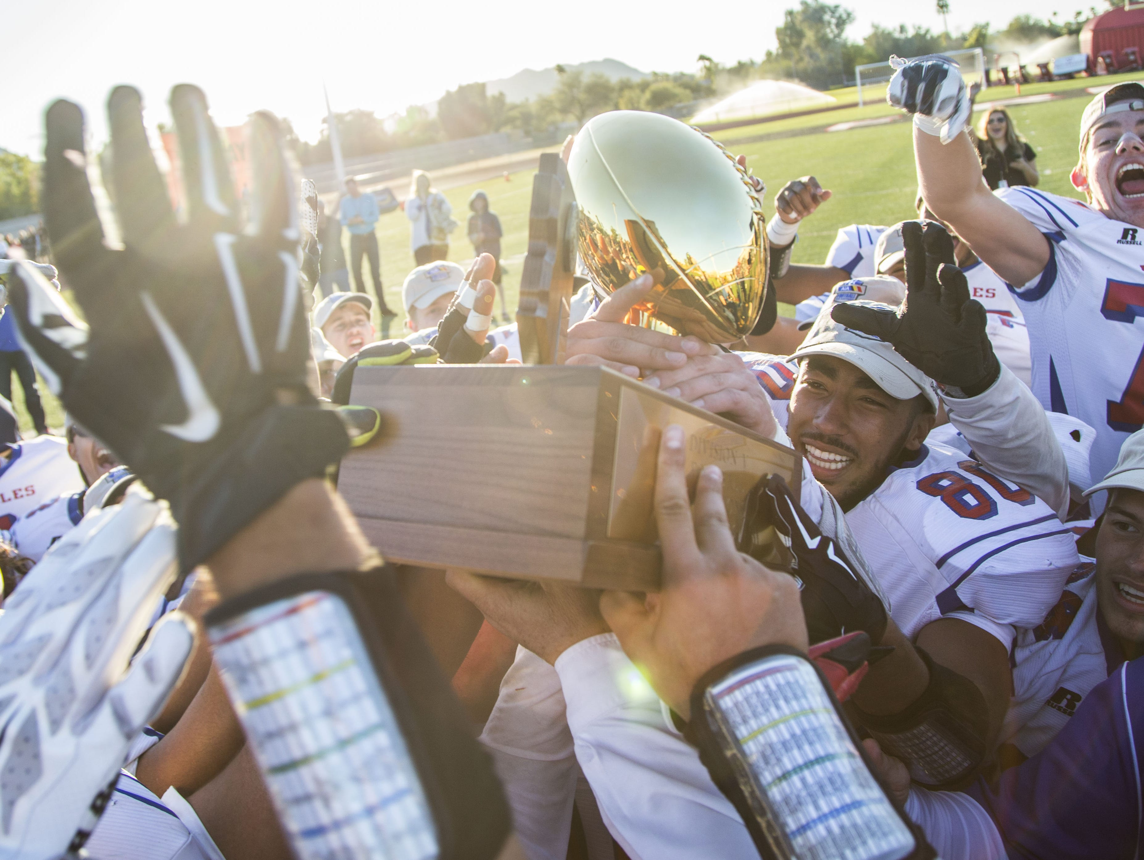 Joy Christian's Isaiah Goodspeed (80) lifts the trophy with his teammates after winning the Division V State Championship against Benson at Chaparral High School on Nov. 28, 2015 in Scottsdale Ariz.