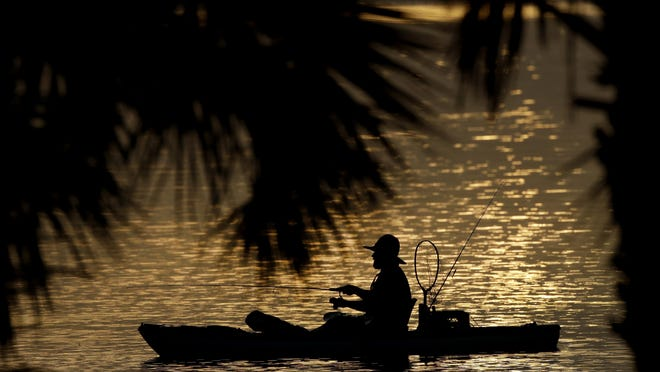 A man fishes in the Indian River Lagoon at sunrise on May 30.