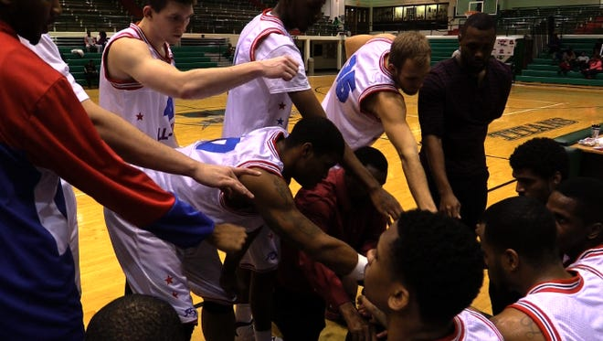 Members of the Indy Naptown All Stars gather around coach, general manager and owner Kevin Jones, as he lays out the team's next play during a home game against ABA opponent Detroit Coast-to-Coast All Stars on Dec. 14, 2014.