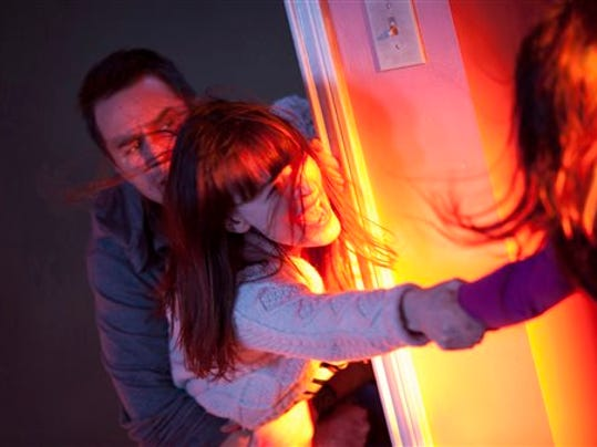 """This photo provided by Twentieth Century Fox shows, Sam Rockwell, left, as Eric Bowen and Rosemarie DeWitt, center, as wife Amy, desperately trying to hold on to Kennedi Clements, right, their youngest daughter Madison, who's been targeted by terrifying apparitions in the film, """"Poltergeist."""" (Kerry Hayes/Twentieth Century Fox  via AP)"""