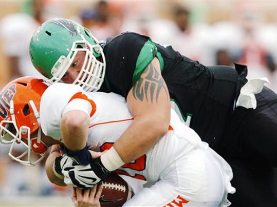 University of North Texas' Richard Abbe (97) tackles University of Texas-El Paso's Mack Leftwich, left, during an NCAA college football game on Saturday, Nov. 9, 2013, in Denton, Texas.