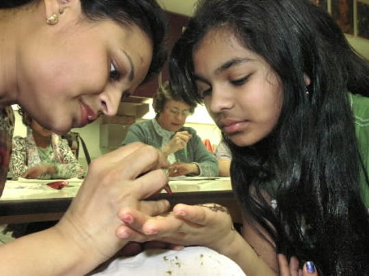 Manju Gupta paints a henna design on her daughter Ayushi Gupta's forearm and hand in this February 2010 file photo.