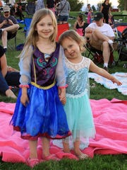 Ruby and Eisley Handy were dressed like the two princesses from the movie they were watching, 'Frozen.' They were among hundreds who enjoyed free movies Friday at Boardwalk Park.