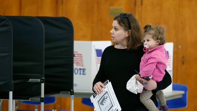 Suzanne Hess holds her 15-month-old daughter Lauren while voting at the United Church of Pittsford.