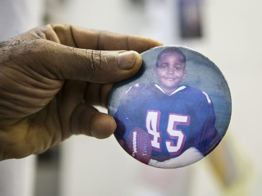 November 10, 2015: Yvens Bernard holds a pee-wee football photo of his son, Giovani Bernard, who is now a Cincinnati Bengals running back. It is pinned to one of the pipes in his dry cleaning shop.