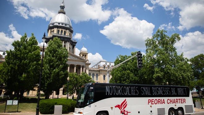 """A rally of motorcoach companies, including Peoria Charter Coach, lineup along Second Street in front of the Illinois State Capitol as they circle the complex during a """"rolling rally"""" to raise awareness of their need for federal assistance as the industry faces financial troubles due to the COVID-19 pandemic, Wednesday, June 17, 2020, in Springfield, Ill. The industry is requesting $15 billion in grants and loans and modifications to Economic Injury Disaster Loan and Paycheck Protection Program to help save the industry. """"Like many local small businesses, my operations have been absolutely devastated by the  coronavirus,"""" Peoria Charter Coach owner Bill Winkler said. """"My buses sit idling while my employees remain at home. We all want to be back  on the road, bringing people from point A to point B while serving our communities again."""""""
