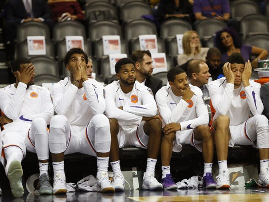 Phoenix Suns players watch the final seconds of their