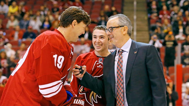 Arizona Coyotes right wing Shane Doan (19) talks with majority owner Andrew Barroway and son Jake prior to a ceremonial puck drop prior to their  NHL game Saturday, Jan. 3, 2015 in Glendale.