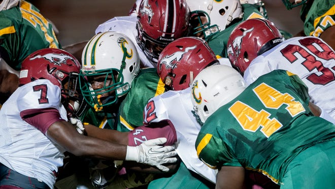 Carver running back Darron Jenkins is swarmed over by  Stanhope Elmore defenders in Millbrook, Ala. on Friday September 18, 2015.