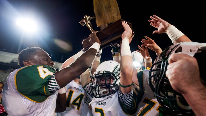 Edgewood's Maurice Young (4) and Daniel Green (2) carry the championship trophy after defeating Marengo at the AISA State Championships in Troy, Ala. on Friday November 20, 2015.