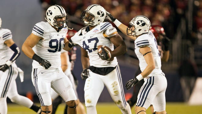 Ezekial Ansah (47) celebrates with Branson Kaufusi (90) after making an interception while playing for BYU in 2012.